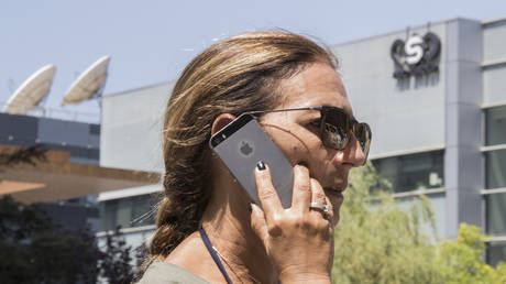 FILE PHOTO. A woman uses her iPhone in front of the building housing the Israeli NSO group. © AFP / JACK GUEZ