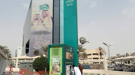 A man withdraws money from an ATM outside the Saudi NCB bank, after an outbreak of coronavirus, in Riyadh, Saudi Arabia
