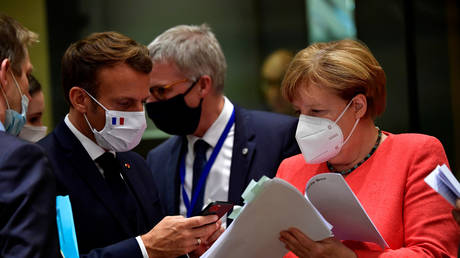 France's President Emmanuel Macron takes pictures from a document held by German Chancellor Angela Merkel during the first face-to-face EU summit since the coronavirus disease (COVID-19) outbreak, in Brussels, Belgium, July 20, 2020