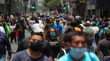 People walk near Zocalo Square during the gradual reopening of commercial activities in Mexico City, Mexico