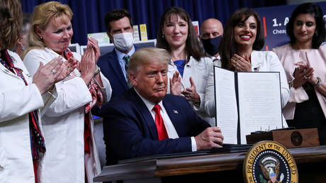 Donald Trump displays an executive order on lowering drug prices during a ceremony at the White House in Washington, July 24, 2020 © Reuters / Leah Millis