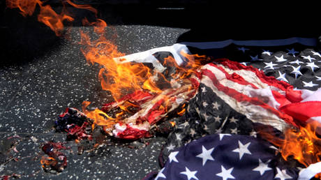 A U.S. flag burns by protesters at Donald Trump's star on the Hollywood Walk of Fame during an anti-Trump rally in in Los Angeles, California, U.S., July 4, 2020