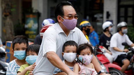 A man and his children, all wearing protective masks, ride a bicycle on a street during the coronavirus disease (COVID-19) outbreak, in Hanoi, Vietnam July 27, 2020. © REUTERS/Kham