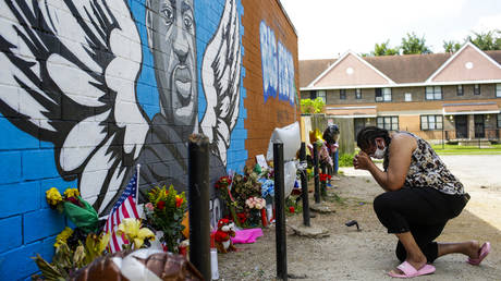 A woman prays outside Scott Food Mart at a makeshift memorial and a mural for George Floyd in the 3rd Ward on June 9, 2020 in Houston, Texas