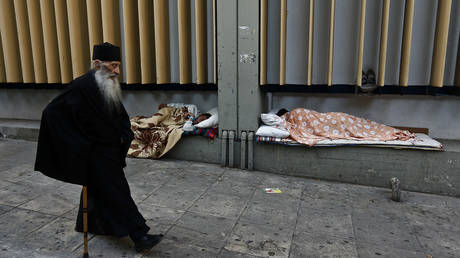 A Greek Orthodox monk walks past two homeless men sleeping outside a hospital in central Athens