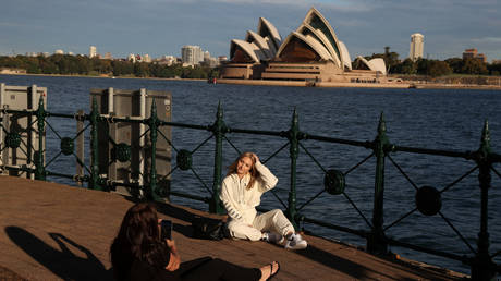FILE PHOTO: A woman poses  in front of the Sydney Opera House, Australia © Reuters / Loren Elliott