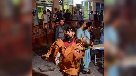 A volunteer carries an injured man to hospital, following a bomb blast attack in a prison in Jalalabad city on August 2, 2020. © AFP / NOORULLAH SHIRZADA