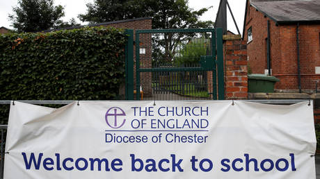 FILE PHOTO: A sign is seen on a fence outside a school in Manchester, UK, on July 2, 2020.