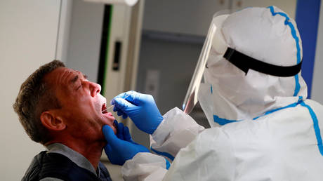 FILE PHOTO: A man gets tested for Covid-19 in Berlin, Germany. August 5, 2020. © Fabrizio Bensch / Reuters