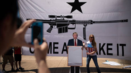 Bill Wang photographs his wife Brooke Wang as she sets a cardboard cutout of U.S. President Donald Trump in front of a banner during an open carry firearm rally on the sidelines of the annual National Rifle Association meeting in Dallas, Texas, U.S., May 5, 2018.