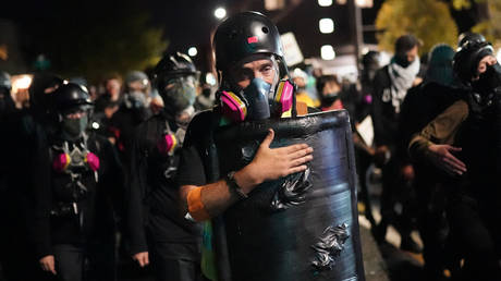 A protesters slaps his shield while marching toward the Portland Police Bureau North Precinct on the 75th day of protests against racial injustice and police brutality on August 10, 2020 in Portland, Oregon. © Getty Images via AFP / GETTY IMAGES NORTH AMERICA /Nathan Howard