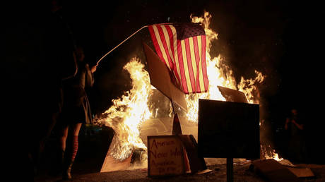 FILE PHOTO: A demonstrator sets fire to an American flag during a protest against police violence in Portland, Oregon.