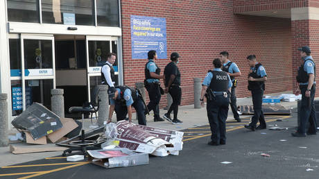 Police officers detain a man who was found inside of a Best Buy store on August 10, 2020 in Chicago, Illinois.