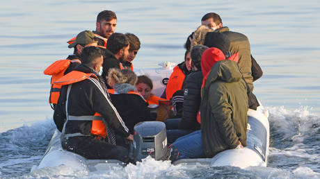 FILE PHOTO: A dingy carries a group of migrants is escorted to the English Border Force by a French patrol boat on the English Channel, 12 miles from Dover on May 27, 2020 at sea