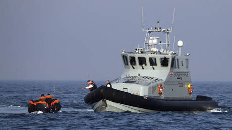 A Border Force vessel assist a group of people thought to be migrants on board from their inflatable dinghy in the Channel, Monday Aug. 10, 2020.