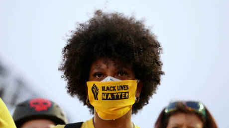 "FILE PHOTO: A protester with the ""Black Lives Matter"" slogan printed on her face mask in Portland, Oregon, U.S., July 26, 2020. © REUTERS/Caitlin Ochs"