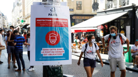 Pedestrians wearing protective face masks walk by a coronavirus disease (COVID-19) information sign in France on August 13, 2020.