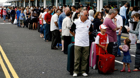 FILE PHOTO: Travelers line up outside a terminal at Gatwick Airport, near Sussex, England.