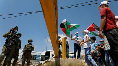 Demonstrators hold Palestinian flags in front of Israeli soldiers during a protest against the UAE deal with Israel to normalize relations in West Bank August on 14, 2020.