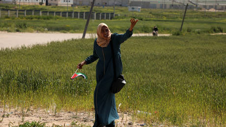 FILE PHOTO: A woman holds a Palestinian flag during an event marking Land Day near the Israel-Gaza border as mass rallies planned to commemorate the event were cancelled amid concerns about the spread of coronavirus disease (COVID-19), east of Gaza City March 30, 2020