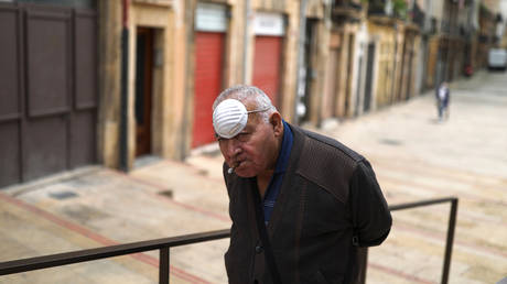 FILE PHOTO. A man wearing a face mask on his forehead smokes a cigar in Tarragona, Spain.
