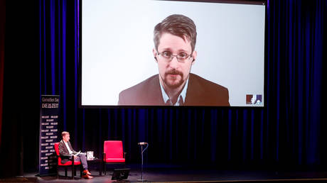 """FILE PHOTO: Edward Snowden speaks via video link as he takes part in a discussion about his book """"Permanent Record"""" with German journalist Holger Stark in Berlin."""