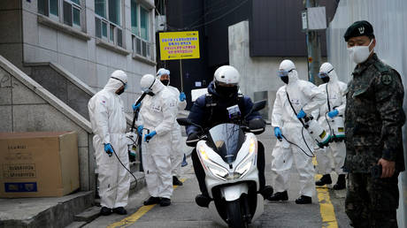 South Korean soldiers in protective gear sanitize a street in Seoul, South Korea, March 6, 2020.