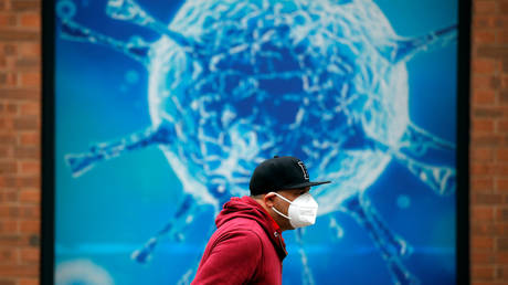 A man wearing a protective face mask walks past an illustration of a virus outside a regional science center in the UK. © REUTERS/Phil Noble/ file photo
