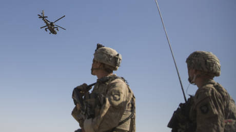 An AH-64 Apache attack helicopter provides security from above while CH-47 Chinooks drop off supplies to U.S. Soldiers with Task Force Iron at Bost Airfield, Afghanistan.© AP / U.S. Marine Corps photo by Sgt. Justin T. Updegraff, Operation Resolute Support