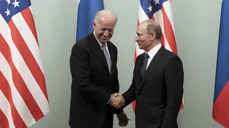FILE PHOTO: Vladimir Putin (R) shakes hands with Joe Biden during their meeting in Moscow March 10, 2011