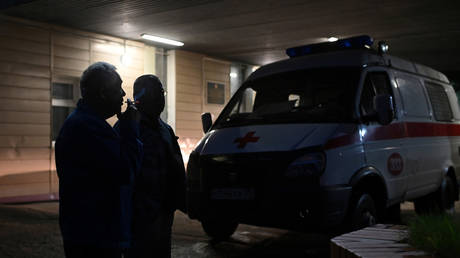 Men stand next to an ambulance outside the hospital where Alexey Navalny was admitted in Omsk, Russia on August 20, 2020.