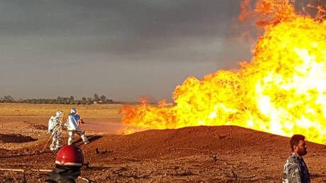 Firefighters extinguishing a burning pipeline in the countryside outside Damascus, Syria on August 24, 2020. © SANA / AFP