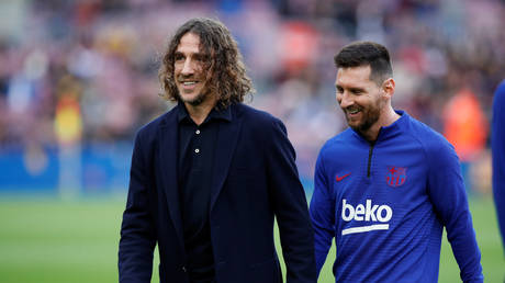 Former Barcelona teammates Carles Puyol and Lionel Messi. © Reuters