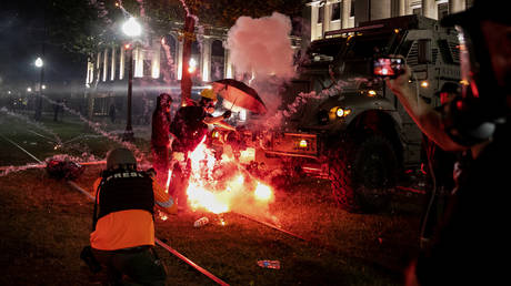 An incendiary device goes off in front of a Kenosha Country Sheriff Vehicle as demonstrators take part in a protest on Tuesday night. © REUTERS/Brendan McDermid