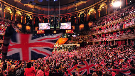 In this file photo taken on September 07, 2013 people wave flags at the Royal Albert Hall in west London on the last night of the Proms. © AFP / CARL COURT