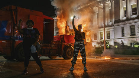 Demonstrators chant in front of a burning truck on August 24, 2020 in Kenosha, Wisconsin. This is the second night of rioting after the shooting of Jacob Blake, 29, on August 23.