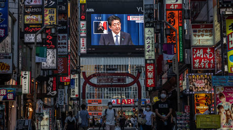 People pass by as Japan's Prime Minister, Shinzo Abe, is displayed on a giant television screen during a press conference in which he announced his resignation on August 28, 2020 in Tokyo, Japan