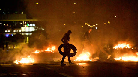 Demonstrators burn tires during a riot in the Rosengard neighborhood of Malmo, Sweden following a public Koran burning, August 28, 2020.