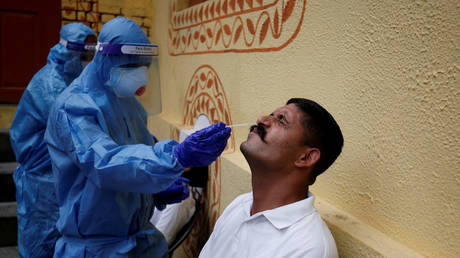 FILE PHOTO: A healthcare worker takes a swab from a police officer for a rapid Covid-19 test in Ahmedabad, India. ©REUTERS / Amit Dave