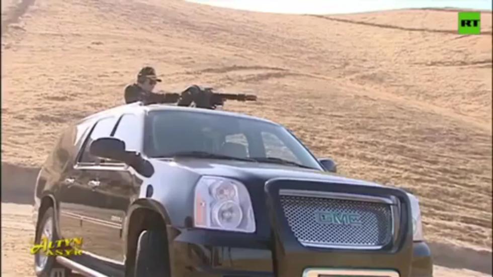 WATCH: Turkmenistan president blows up explosive barrels with car-mounted MACHINE GUN in latest bizarre stunt
