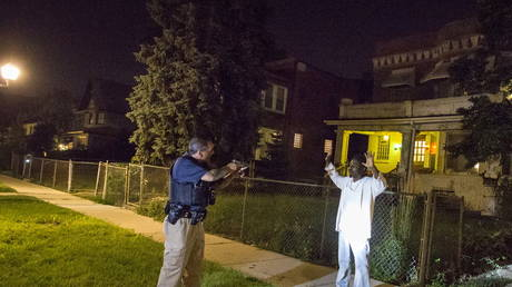 FILE PHOTO: A Cook County Sheriff's deputy points his gun at a man who approached police while they were conducting an unrelated street stop in the Austin neighborhood in Chicago, Illinois.