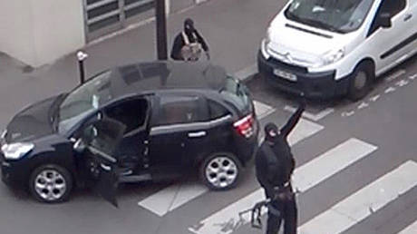 FILE PHOTO Gunmen gesture as they return to their car after the attack outside the offices of French satirical weekly newspaper Charlie Hebdo © REUTERS/Reuters TV