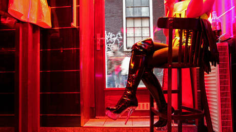 A prostitute, called Eve, waits for clients behind her window in the red light district of Amsterdam. © AFP / ANOEK DE GROOT