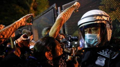 Des manifestants s'affrontent avec un agent de sécurité près d'une clôture autour de la Maison Blanche lors d'une manifestation à Washington, DC, le 27 août 2020 © Reuters / Andrew Kelly