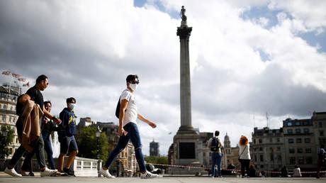 People wearing face masks walk through Trafalgar Square in London, UK. © REUTERS/Henry Nicholls