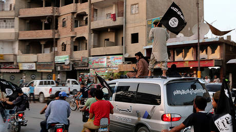 Members loyal to the ISIL wave ISIL flags as they drive around Raqqa © Reuters
