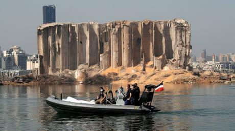 Des membres de l'armée libanaise et de l'armée française montent à bord d'un bateau devant le silo à grains endommagé près du site de l'explosion massive dans la zone portuaire de Beyrouth.  © Reuters / Gonzalo Fuentes