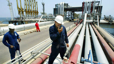 FILE PHOTO: Refinery workers check the valves of a filling platform at the El Palito refinery, 150 miles west of Caracas.
