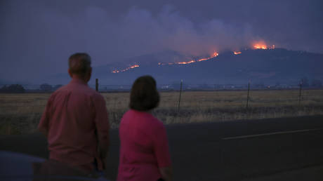 Local residents look at smoke and fire over a hill during wildfires near the town of Medford, Oregon, September 9, 2020 © Reuters / Carlos Barria