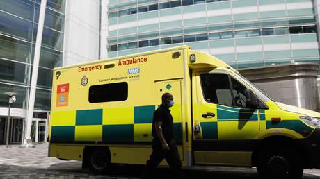 FILE PHOTO: A man walks past an ambulance at University College Hospital in London on July 17, 2020. © Tolga Akmen / AFP
